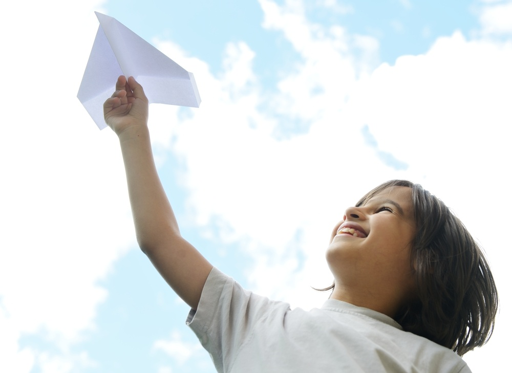 Child holding a paper airplane and dreaming about traveling.jpeg