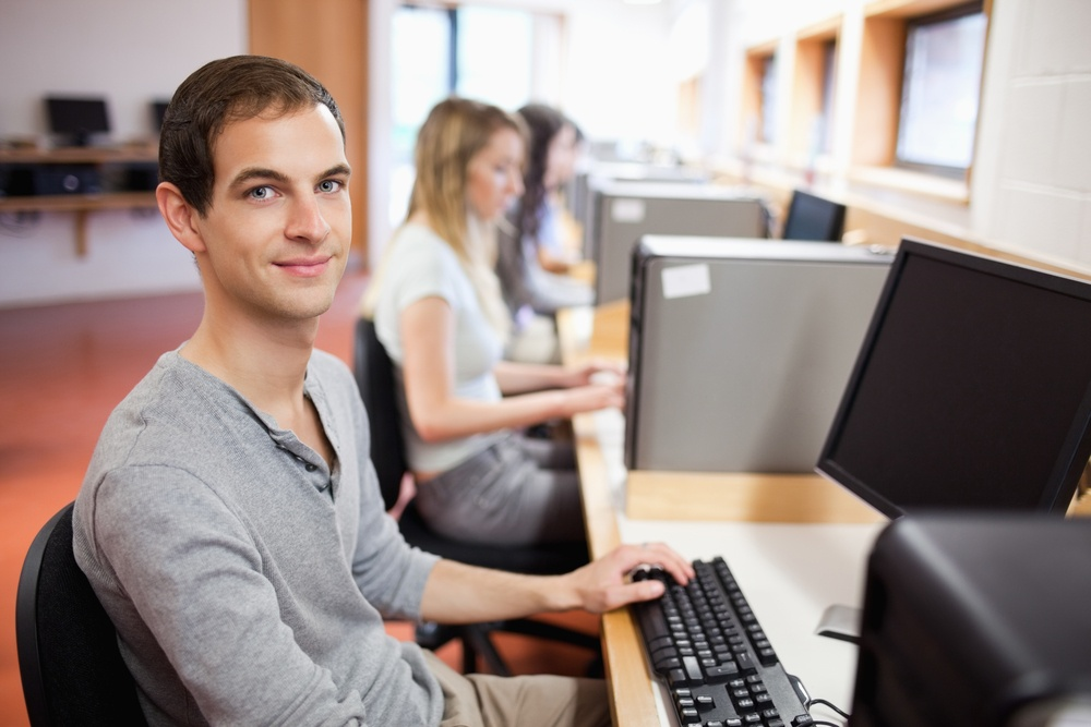 Smiling male student posing with a computer in an IT room.jpeg class=